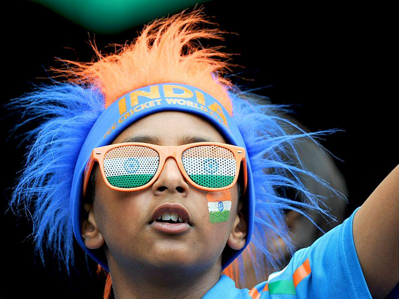 An Indian supporter, with his face painted and wearing colourful glasses, arrives before the start of the Cricket World Cup against South Africa at the Melbourne Cricket Ground (MCG) February 22, 2015.  REUTERS