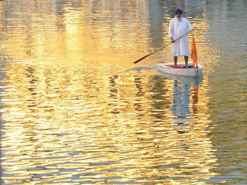 A man stands on a raft as he performs cleansing work of the Sarowar or the sacred pond of the Golden Temple in Amritsar. Sameer Sehgal/HT