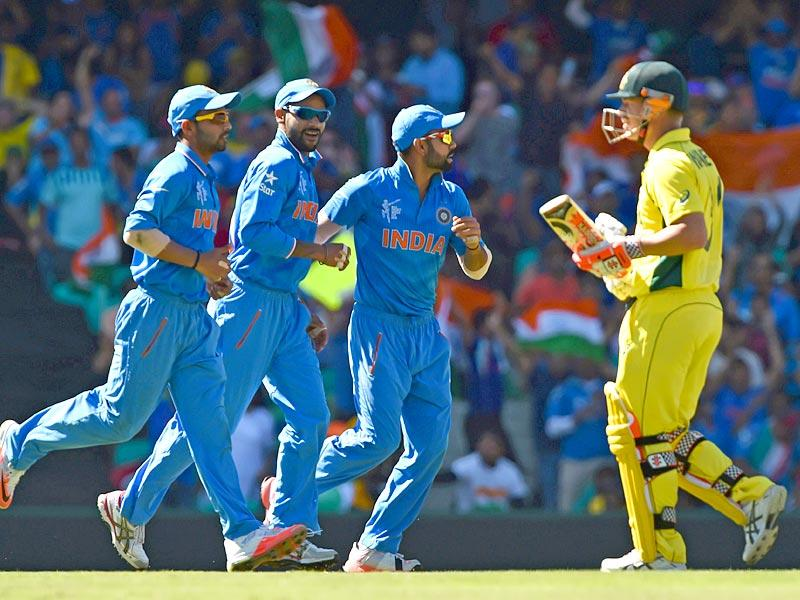 India's players celebrate as Australia's batman David Warner walks off after being dismissed during the 2015 Cricket World Cup semifinal match between Australia and India in Sydney on March 26, 2015. AFP PHOTO