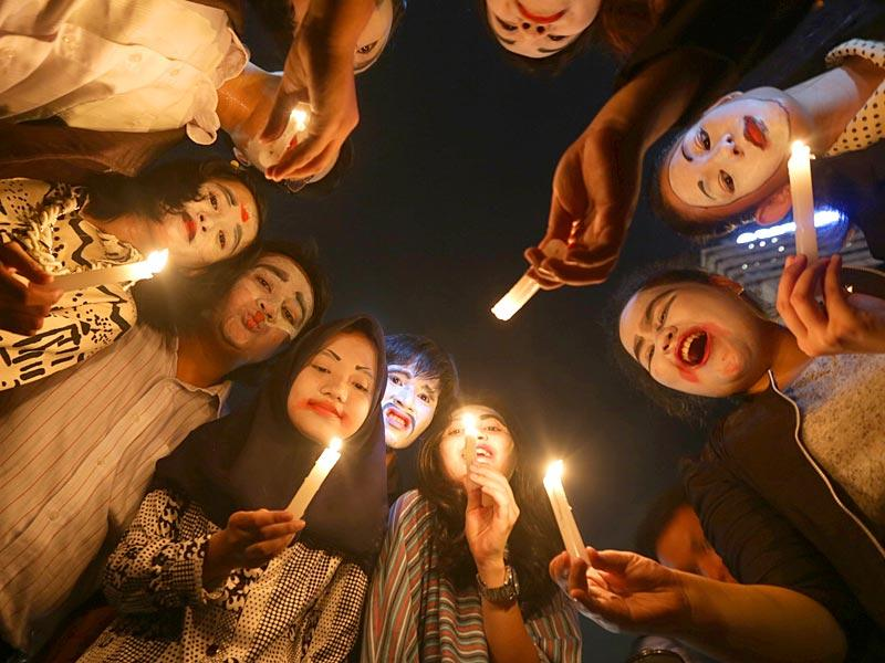 Indonesian activists hold candles during a candle light vigil marking Earth Hour in the main business district in Jakarta. (AP Photo)