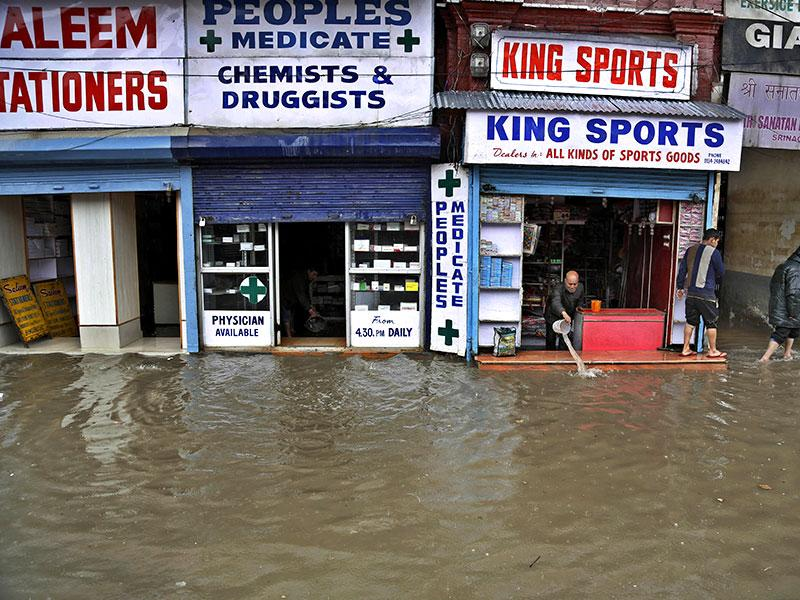Shopkeepers try to remove water from a water-logged footwear shop. (AP Photo)