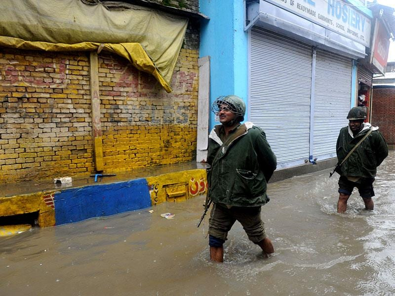 Members of the Central Reserve Police Force (CRPF) walk along a flooded road in Srinagar. (AFP Photo)