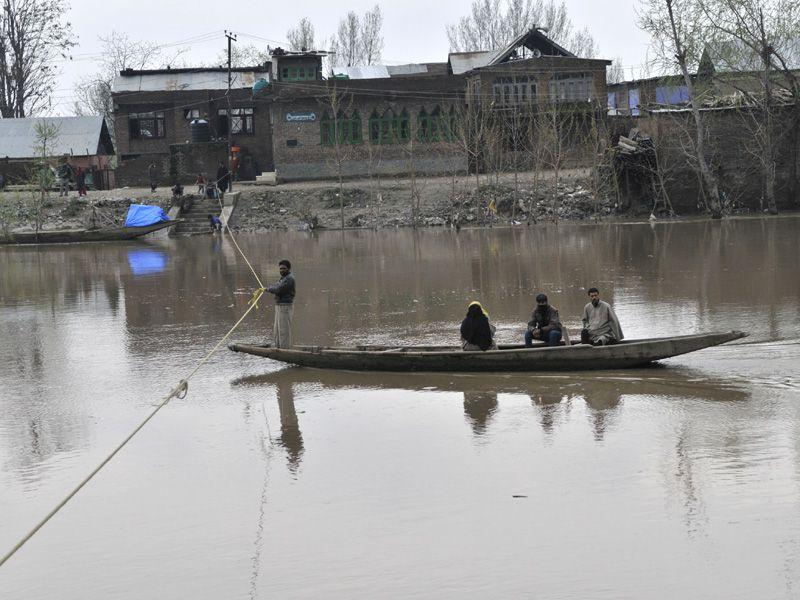 People of Kashmiri crossing the river Jhelum. Emergency workers have recovered 15 bodies including that of a three-week-old baby after a landslide triggered by heavy rains buried several houses. Waseem Andrabi/HT