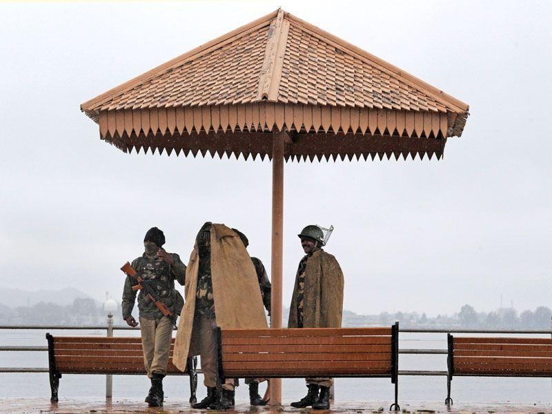 Indian federal paramilitary troops shelter as rain falls on the banks of Dal Lake in Srinagar.AFP/PHOTO