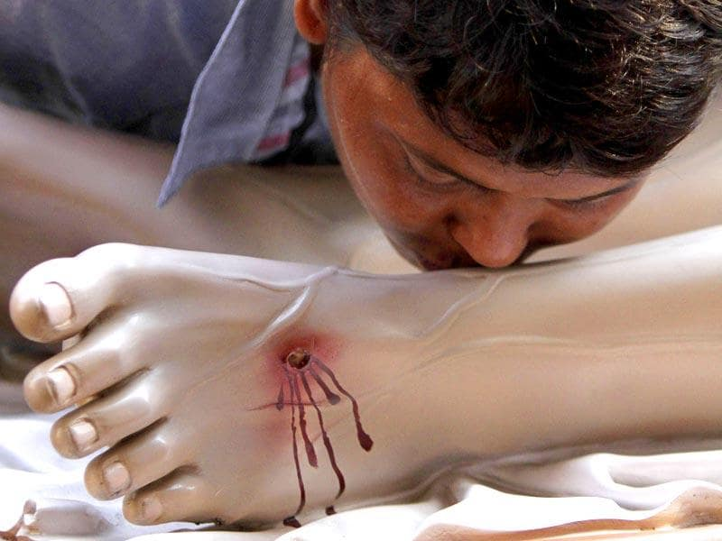 An Indian Christian kisses the feet of a clay model of Jesus Christ on Good Friday in Kolkata. AP Photo