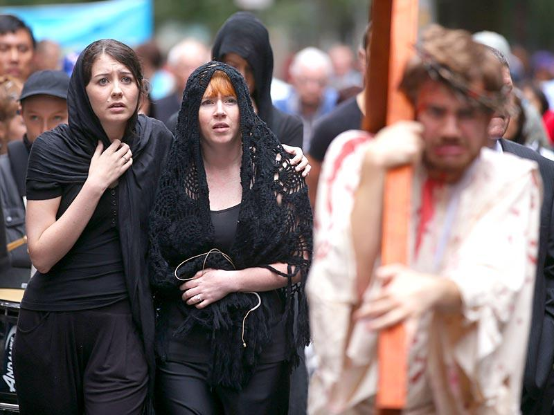 Brendan Paul, right, plays the part of Jesus as supporters follow during a re-enactment of the crucifixion of Christ in Sydney. AP Photo