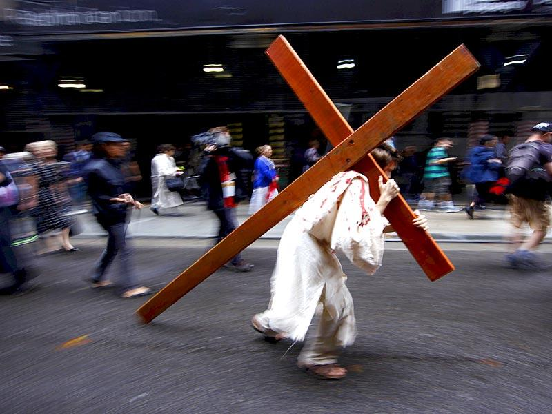A man portraying Jesus Christ carries a wooden cross during a re-enactment of the crucifixion, through the streets of central Sydney on Good Friday.