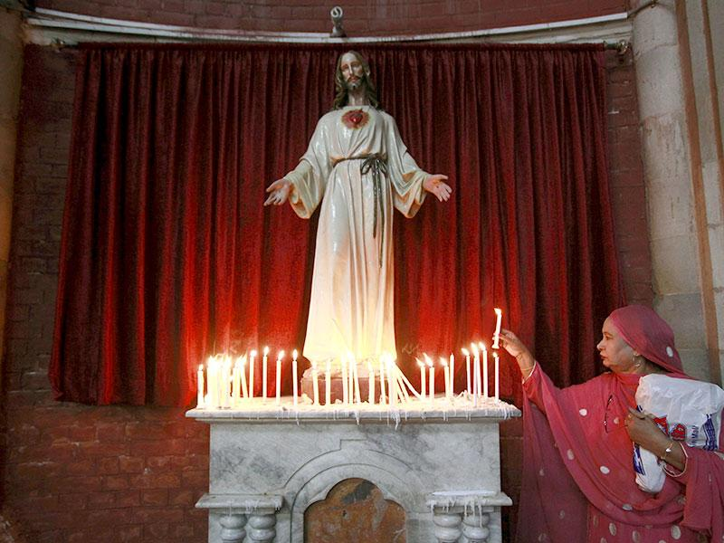 A Pakistani Christian woman lights a candle in front of a religious statue during Easter celebrations at the Sacred Heart of Jesus Church in Lahore. (Reuters Photo)