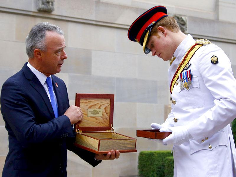 Prince Harry, right, is presented with a gift from Brendan Nelson, director of the Australian War Memorial during a visit the Australian War Memorial in Canberra, Australia. (AP Photo