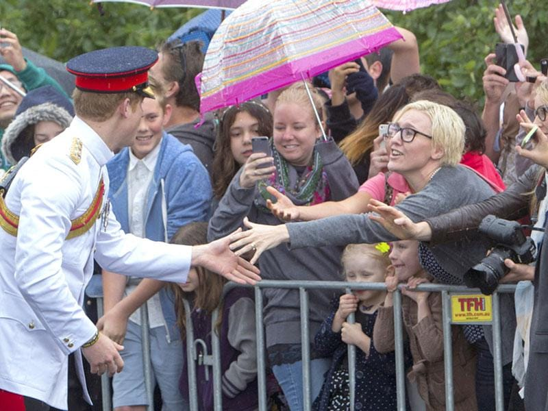 Prince Harry, second left, meets well wishers after laying a wreath at the Tomb of the Unknown Soldier at the Australian War Memorial in Canberra.(AP Photo)