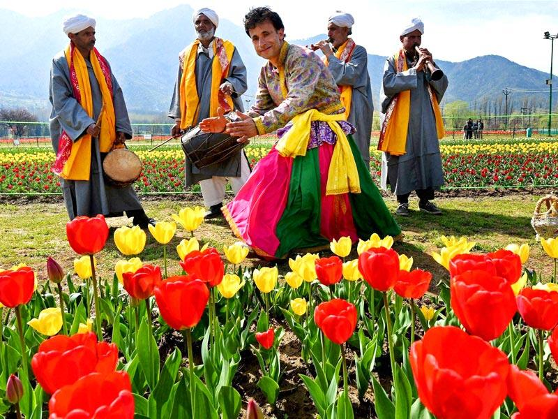 Kashmiri artists perform at the Asia's largest Tulip garden after it was opened for public viewing in Srinagar. (PTI Photo)