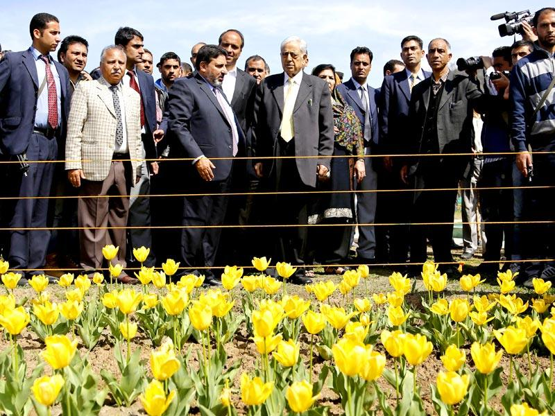 Jammu and Kashmir State Chief Minister Mufti Mohammad Sayeed, center wearing a yellow tie, admires tulips during the season's opening of Siraj Bagh, claimed to be the largest tulip garden in Asia, on Zabarwan Hills in Srinagar. (AP Photo)