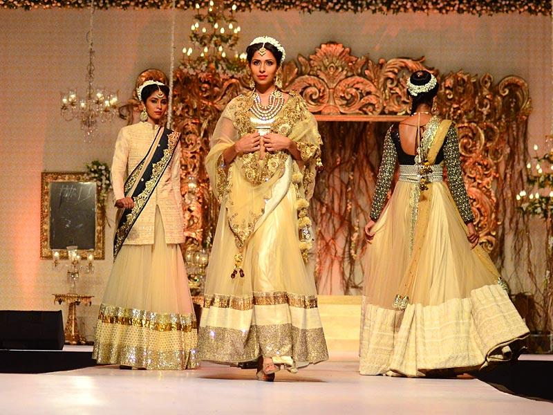 Models walks the ramp in stunning off white and gold Vikram Phadnis ensembles at Wedding Fair 2015 in Mumbai. (IANS)