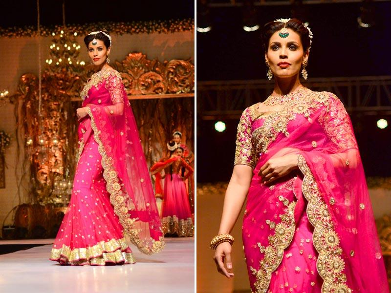 A model walks the ramp in a magenta pink and gold sari designed by Vikram Phadnis at Wedding Fair 2015 in Mumbai. (IANS)