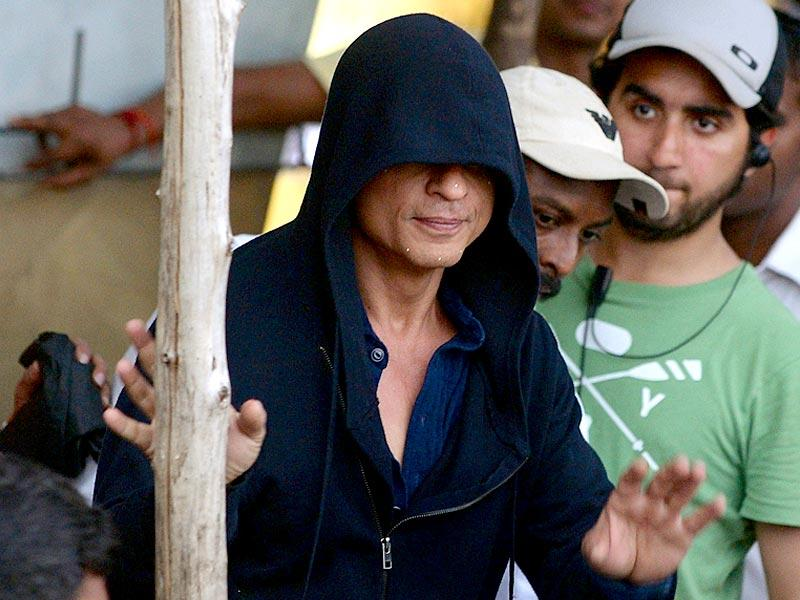 Shah Rukh Khan, face covered in a hood, waves towards fans as he leaves after finishing the on-location shoot in Mumbai on April 6, 2015. (AFP Photo)
