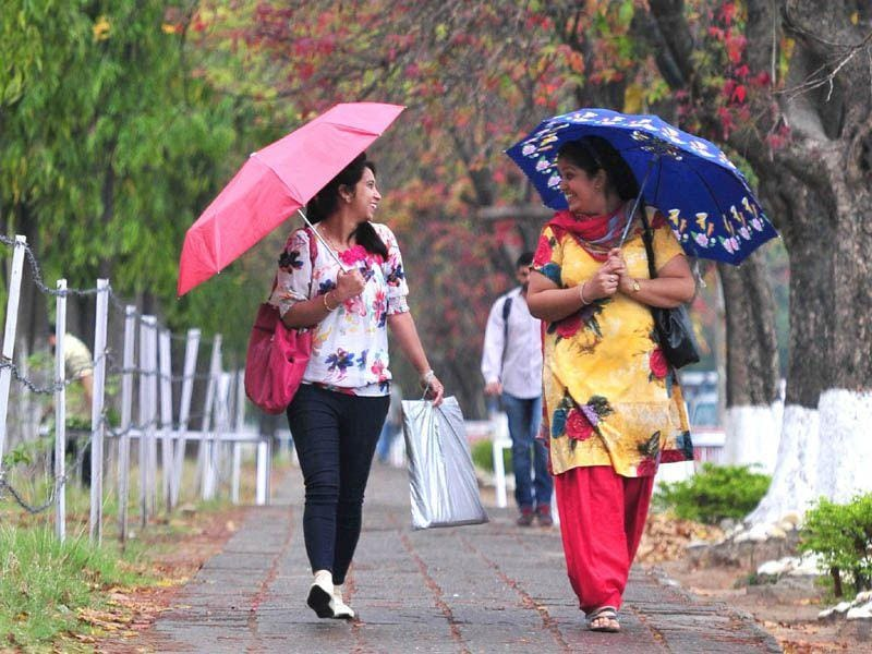 Girls shielding themselves as rains lashed Chandigarh on Tuesday. Ravi Kumar/HT