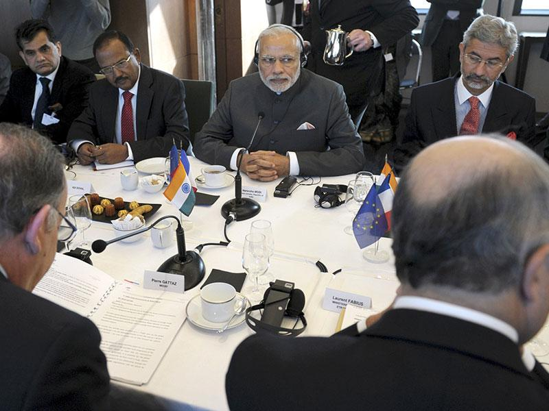 Indian Prime Minister Narendra Modi (C) listens to French employers' association, Medef, head Pierre Gattaz (L) and French Foreign Minister Laurent Fabius (R) at the Medef headquarters in Paris. (AFP Photo)