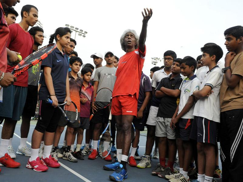 Renowned tennis player Anand Amritraj gives tips to the budding players in Indore on Friday. (Arun Mondhe/HT photo)