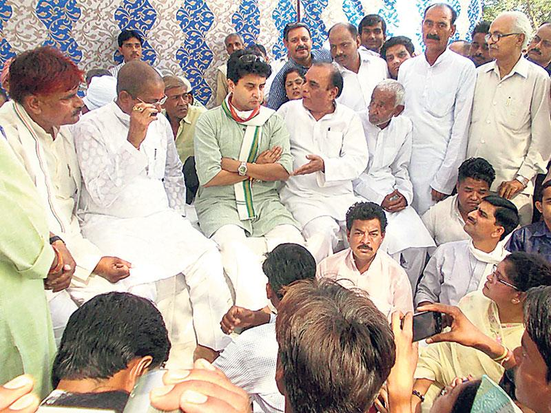 Jyotiraditya Scindia with family members of the farmers who died recently after their crops were destroyed due to hailstorm, in Bhind on Saturday. (HT photo)