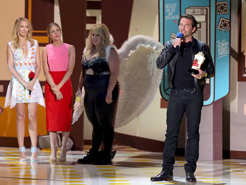 As Bradley Cooper accepts his best actor award, it is hard to miss Rebel Wilson in a pair of wings in the background. (Reuters)