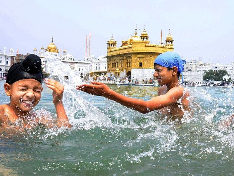 Devotees taking bath in the holy Sarovar and paying obeisance at the Golden Temple in Amritsar on the occasion of Baisakhi. (PTI Photo)