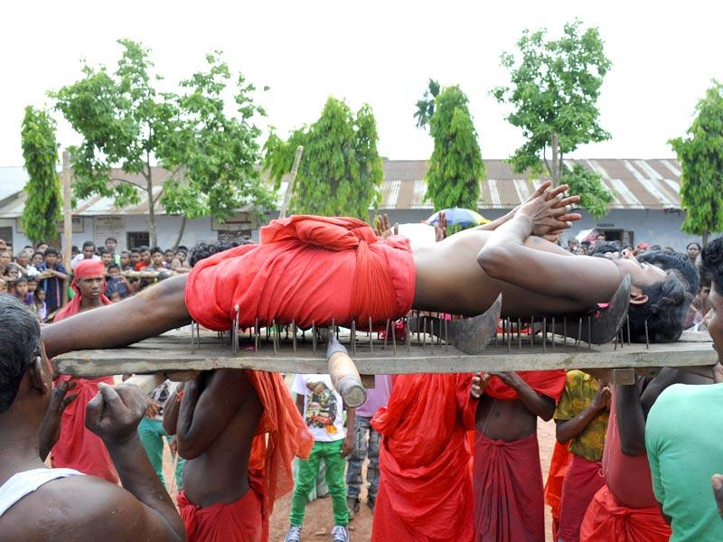 A Hindu devotee lies on a bed of nails as he is carried past spectators during the ritual of Shiva Gajan at Pratapgarh village in Agartala, the capital of northeastern state of Tripura on Tuesday. (AFP Photo)
