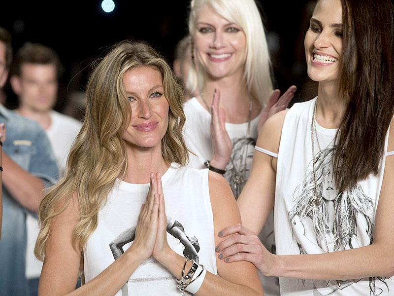 Gisele Bundchen, left, and fellow Brazilian models smile at the end of the show from the Colcci Summer collection. (AP)