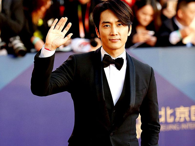 South Korean actor Song Seung-heon waves as he walks the red carpet during the Beijing International Film Festival, in Beijing, April 16, 2015. (Reuters)