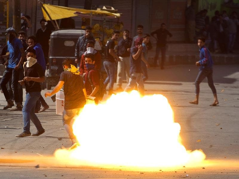 A tear gas shell fired by policemen explodes near Kashmiri protestors in Srinagar, Kashmir. (AP Photo)