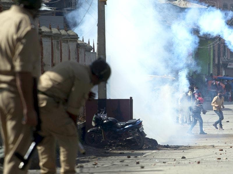 A protester throws back an exploded tear gas shell towards policemen during a protest in Srinagar, Kashmir. (AP Photo)