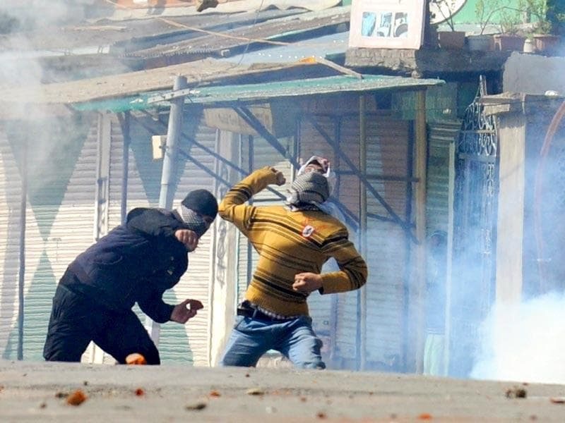 Kashmiri protestors throw stones towards police during clashes in Srinagar, Kashmir. AFP Photo