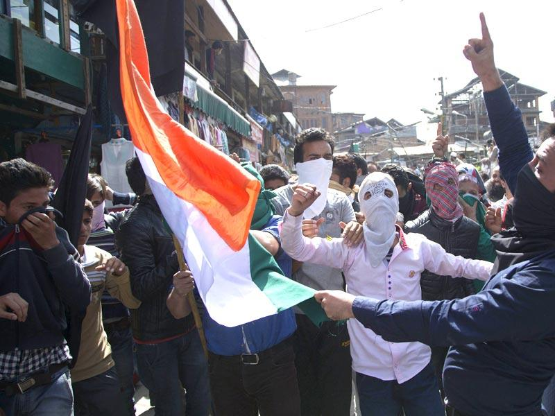 Protesters shout slogans and burn the national flag during a protest in Srinagar, Kashmir. AFP Photo