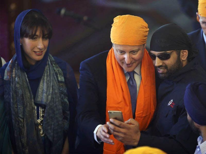Britain's Prime Minister David Cameron, centre, poses for a selfie with a worshipper as Samantha Cameron, left, looks on as they take part in the Vaisakhi festival at Guru Nanak Darbar Gurdwara temple on Saturday.AP