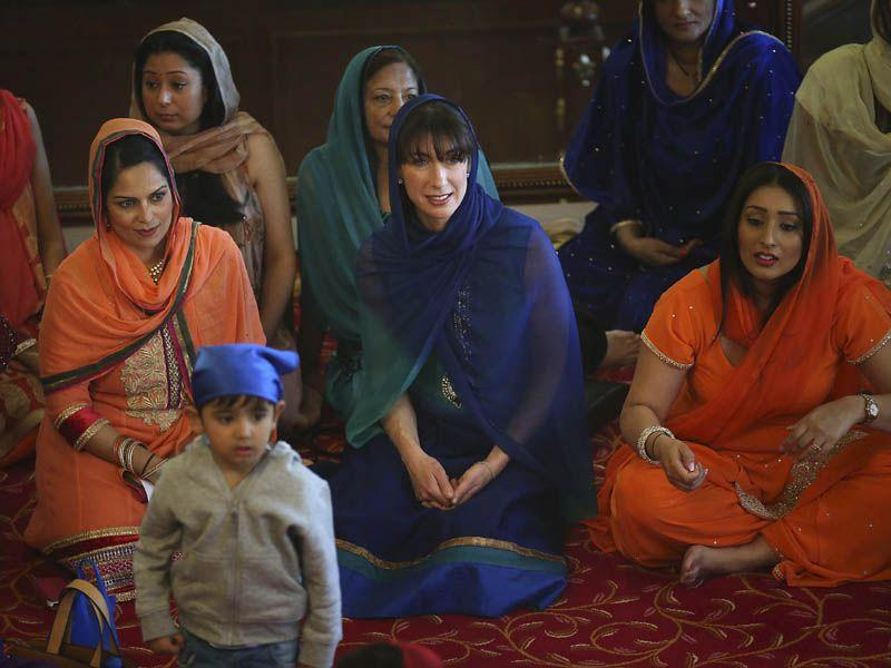 Britain's Prime Minister David Cameron's wife, Samantha, centre, sits with Conservative party Parliamentary candidate Priti Patel, centre left, during the Vaisakhi festival at Guru Nanak Darbar Gurdwara temple on Saturday.AP
