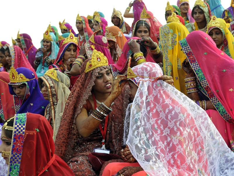 Brides help each other in getting ready during a mass marriage ceremony organised on the occasion of Akshay Tritiya in Bhopal. (Praveen Bajpai/HT photo)