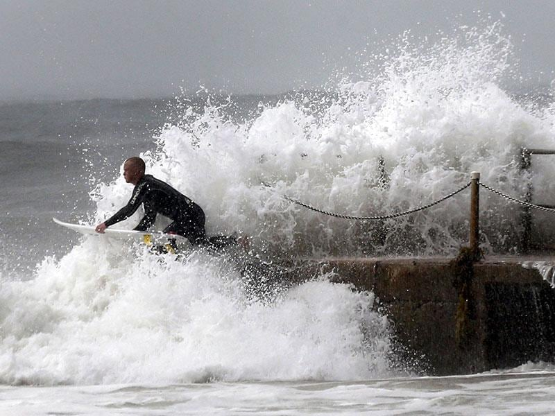 A surfer dives into the Pacific Ocean from a saltwater pool at Sydney's Collaroy Beach as a cyclonic storm lashes Sydney and it's surrounding areas. (Reuters Photo)
