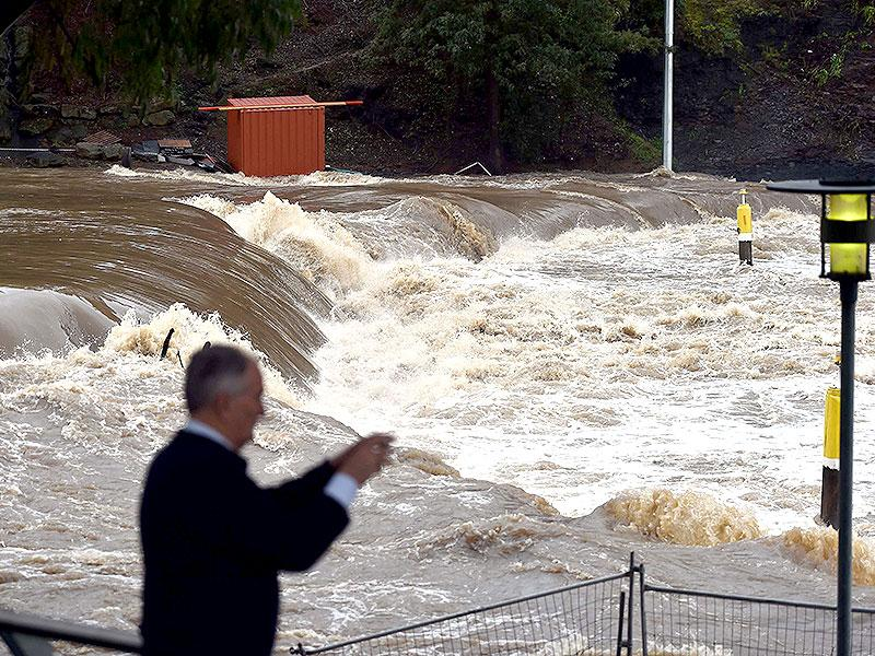 A man takes pictures of flood waters entering the Parramatta ferry wharf in Sydney. (AFP Photo)