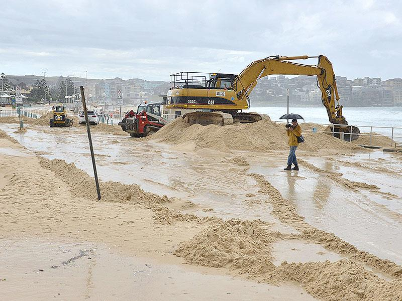 An excavator moves dislodged sand on Sydney's Bondi Beach as the city battles cyclonic wind gusts and non-stop downpours. (AFP Photo)