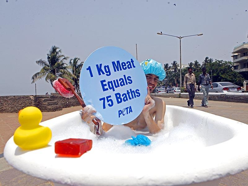 A PETA supporter poses for photos in a bath during a campaign to promote vegetarianism ahead of Earth Day at Carter road, Bandra in Mumbai. (Pratham Gokhale/HT photo)