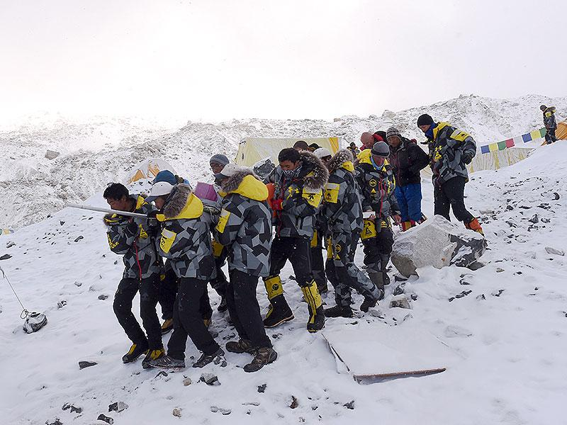 An injured person is carried by rescue members to be airlifted by rescue helicopter at Everest Base Camp. (AFP Photo)