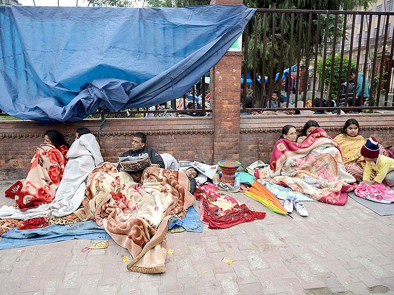 Nepalese residents rest as they gather on a pavement in Kathmandu, a day after an earthquake hit the city. (AFP Photo)
