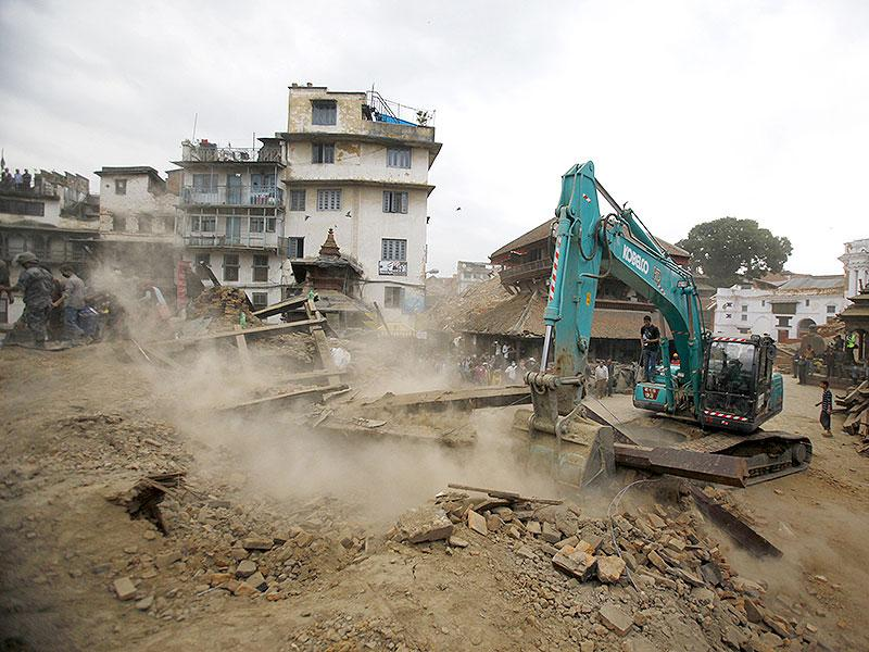 A crane removes debris from the site of a building that collapsed in an earthquake in Kathmandu, Nepal. (AP Photo)