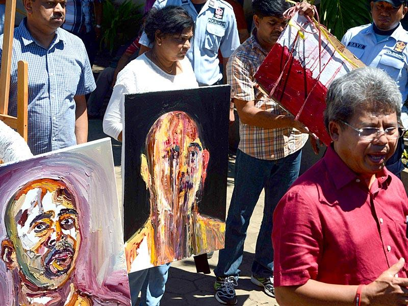 Indonesian lawyer Todung Mulya Lubis (R) displays recent paintings done in prison by Australian drug convict and death row prisoner Myuran Sukumaran at the Nusakambangan port in Cilacap across from the Nusakambangan maximum security prison island. (AFP Photo)