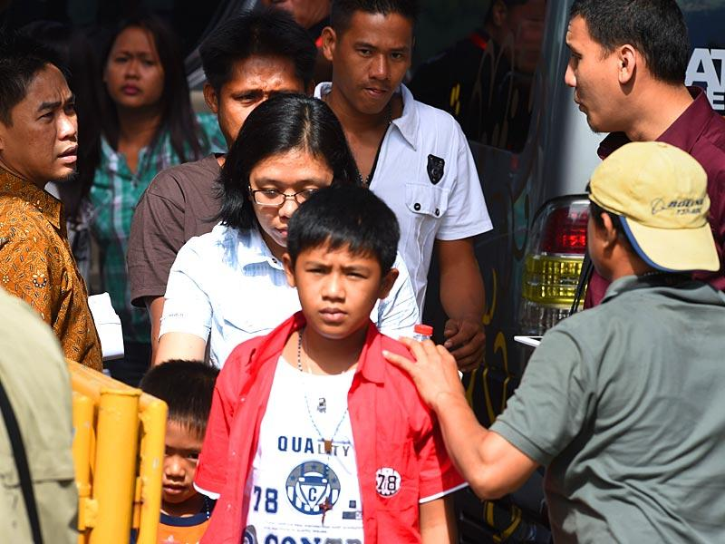 The two sons of death row prisoner Mary Jane Veloso, Mark Danielle (C), 12-years old and Mark Darren, (L bottom partly covered), 6, accompanied by family members as they arrive at Nusakambangan port in Cilacap to visit their mother. (AFP Photo)