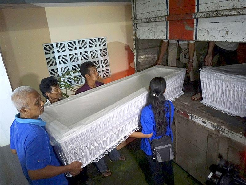 Workers load coffins from a church storage area ready to be taken to a police station in Cilacap, near the prison island of Nusakambangan. (Reuters)