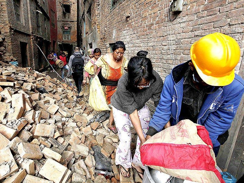 People carry their belongings as they walk past by a damaged site in Kathmandu. (Raj K Raj/HT Photo)