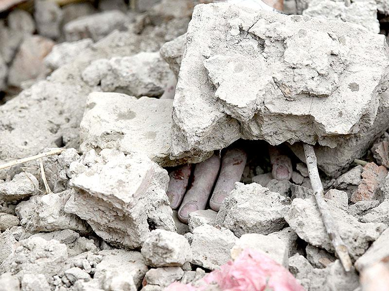 The body of a victim remains buried under the rubble of a damamged building in Kathmandu. (Raj K Raj/HT Photo)