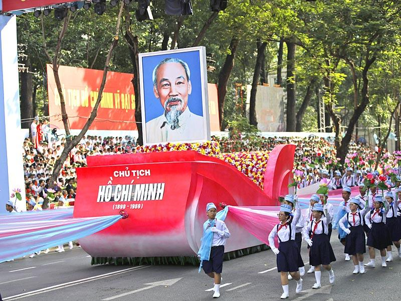 School children walk alongside a float carrying a portrait of Vietnamese national hero Ho Chi Minh during the parade. (AP Photo)