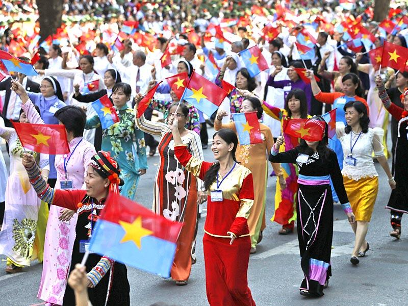 Vietnamese women wave the National Liberation Front's and Vietnamese national flags during the parade. (AP Photo)