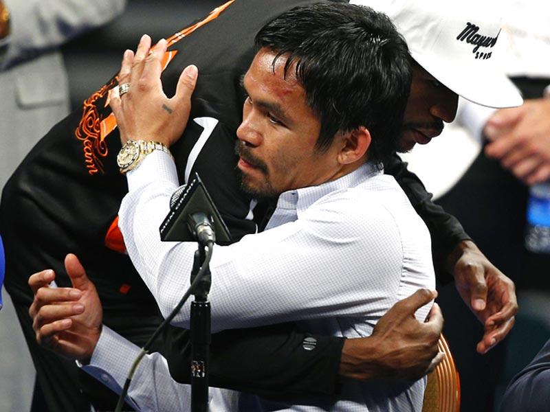 Manny Pacquiao is embraced by Floyd Mayweather Jr. during a press conference following their welterweight title fight. (AP Photo)